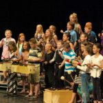 "Director Carol Glidden leading the Jack Stuart School, Grade 5 performers in ""Buy Me Chocolate""."