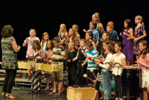 "Director Carol Glidden leading the Jack Stuart School, Grade 5 performers in ""Buy Me Chocolate"""